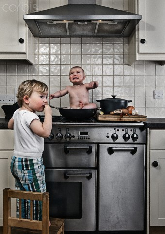 Young boy (3-4) caught cooking baby brother (1-6 months) on stove --- Image by © Justin Paget/Corbis